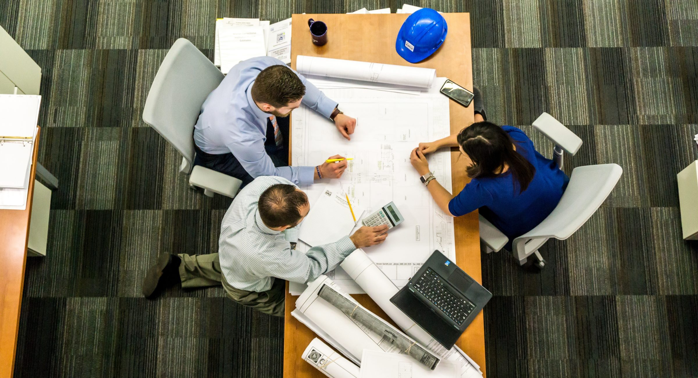 Overhead shot of people sitting around a table looking at blueprints